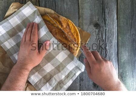 Górę widoku człowiek piekarz cięcie chleba Zdjęcia stock © deandrobot