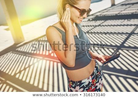 Gelukkig luisteren naar muziek mobiele telefoon permanente Stockfoto © deandrobot