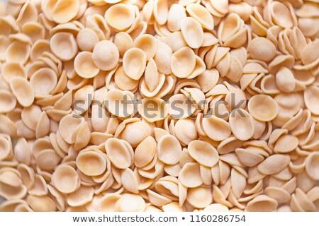 raw uncooked italian orecchiette pasta food background blur defocused stock photo © zkruger
