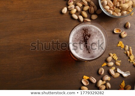 glass of beer, smartphone and pistachio on table Stock photo © dolgachov