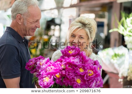 charming senior woman buying flowers on market stock photo © boggy