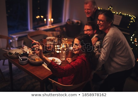 woman calling on smartphone at christmas dinner stock photo © dolgachov