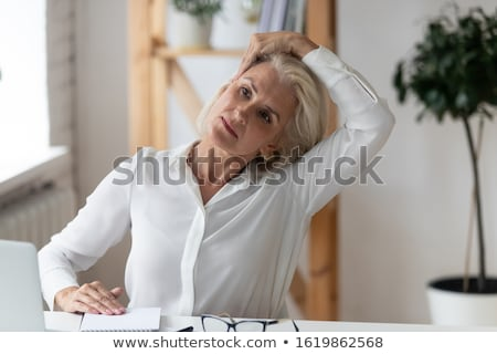 middle aged female employee doing exercises in the office stock photo © elnur