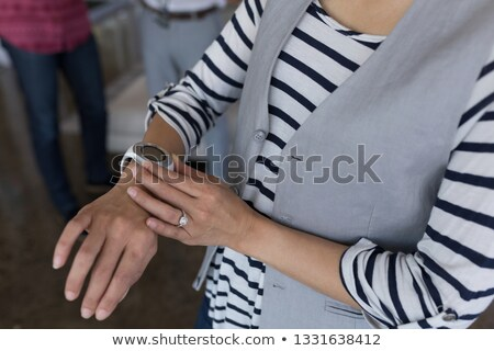 Mid section of casually dressed beautiful mixed-race female executive using smartwatch in modern off Stock photo © wavebreak_media