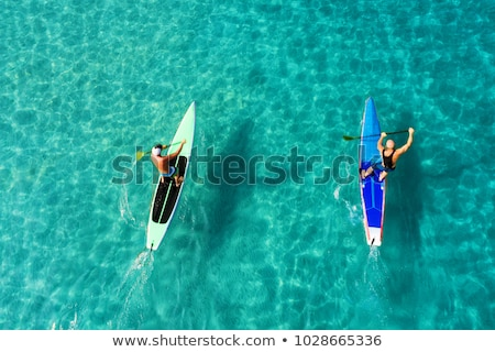 Strong men floating on a SUP boards in a beautiful bay on a sunny day. Aerial view of the men crosse Stock photo © galitskaya