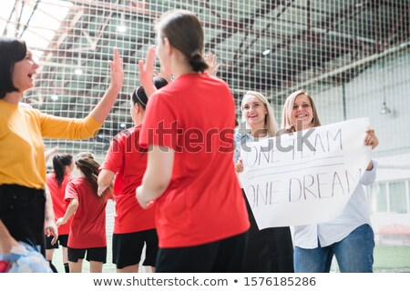 One of sports girls giving high-five to fan or friend while going out to field Stock photo © pressmaster