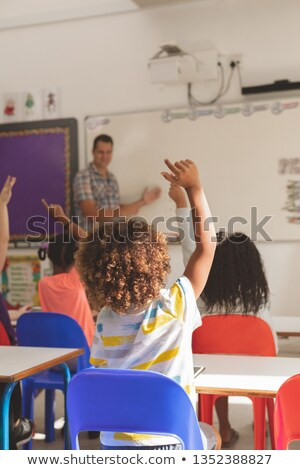 Rear view of school kids raising hand to answer at a question while the teacher speaking at whiteboa Stock photo © wavebreak_media