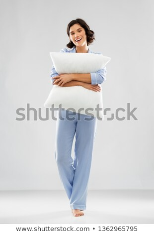 happy young woman in blue pajama hugging pillow Stock photo © dolgachov