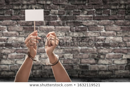Handcuffed Female Hand Holding Blank Sign Against Aged Brick Wal Stock photo © feverpitch