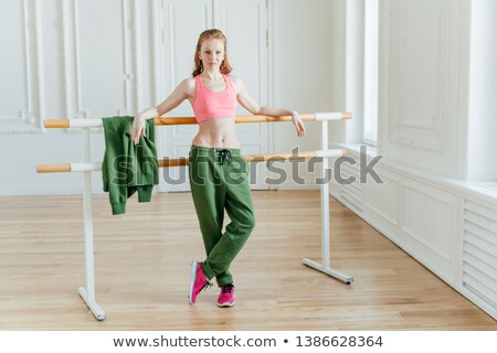 Slim beautiful female ballet dancer leans at ballet barre, wears pink top, sport trousers and sneake Stock photo © vkstudio