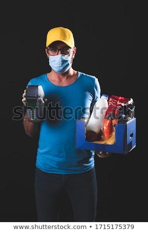 Man in medical mask prevents coronavirus disease holds a poster home prison Hand written text - lett Stock photo © galitskaya