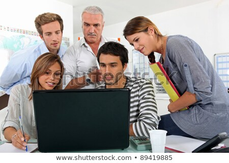 a bunch of people gathered behind a laptop Stock photo © photography33