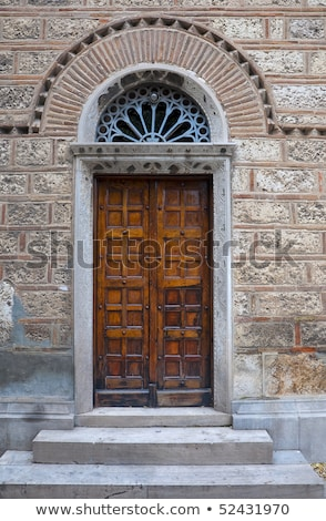 A stone cross on an old, carved, wooden church porch stock photo © TheFull360