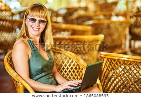 ストックフォト: Young Woman In Sunglasses On Chair Outdoor Looking At Laptop