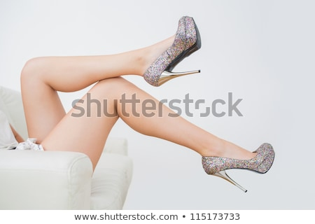 Stock photo: legs and high heels shoes relaxing on a sofa