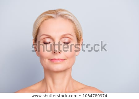 portrait of beautiful smiling woman with closed eyes on gray background stock photo © deandrobot
