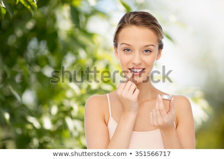 jonge · vrouw · balsem · lippen · glimlachend · gezicht - stockfoto © dolgachov