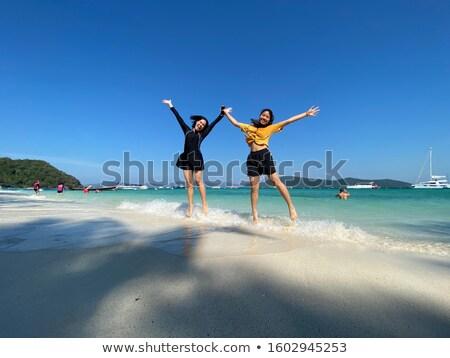 Two asian teen girls friends jumping enjoy on the beach stock photo © Yongkiet