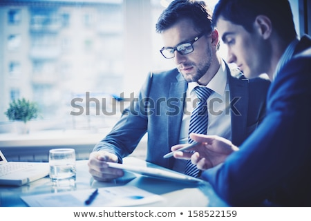 businessmen discussing project at meeting pointing explaining hi Stock photo © snowing