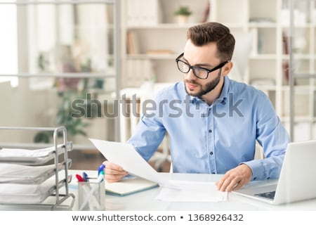 Stock photo: Young serious economist or trader reading financial papers