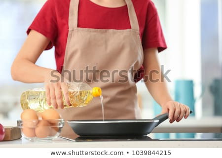 Woman pouring cooking oil on vegetable in kitchen at home Stock photo © wavebreak_media