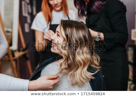 Hairdresser hairstyling the client's hair Stock photo © Kzenon