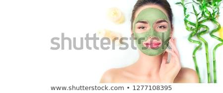 Spa Woman applying Facial green clay Mask. Beauty Treatments. Fresh green smoothie with banana and s Stock photo © galitskaya