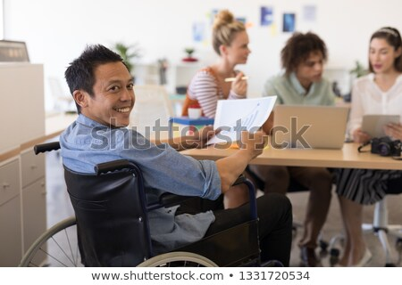 Portrait of disabled Asian male executive holding paper with graph in modern office Stock photo © wavebreak_media