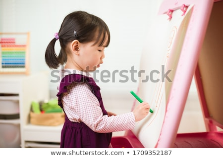 Girl toddler paint with chalk on a blackboard stock photo © galitskaya
