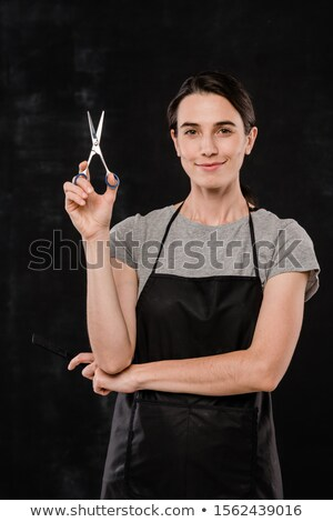 Pretty young hairdresser in apron holding sharp scissors to cut your hair Stock photo © pressmaster