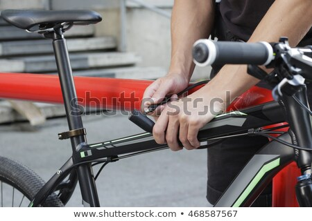 man fastening bicycle lock on street parking Stock photo © dolgachov