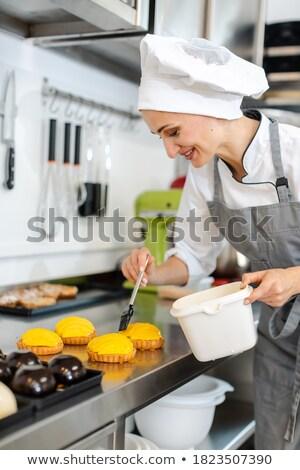Confectioner working on sweet little cakes Stock photo © Kzenon
