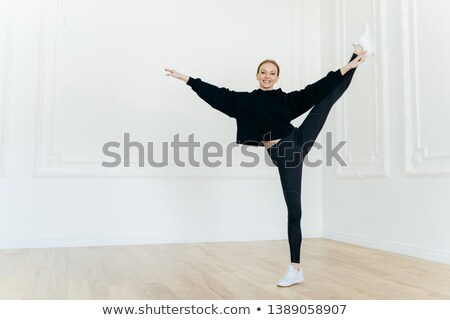 Fit athtletic woman demonstrates resiliance, balances on one leg, being skilled sport gymnast, dress Stock photo © vkstudio