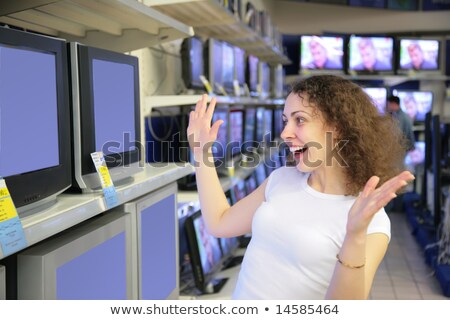 young woman in delight looks at TVs in shop Stock photo © Paha_L