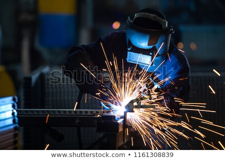 Arc welder worker in protective mask welding metal construction Stock photo © ia_64