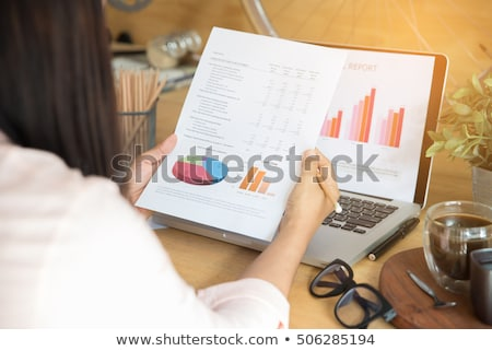 Businesswoman reviewing annual report Stock photo © stockyimages