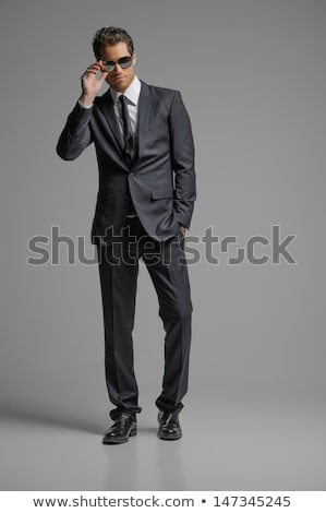 Handsome man in sunglasses and formalwear posing and looking away Stock photo © deandrobot
