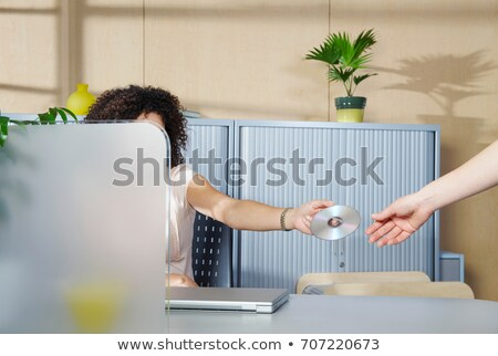 Woman handing over DVD to co-worker Stock photo © IS2