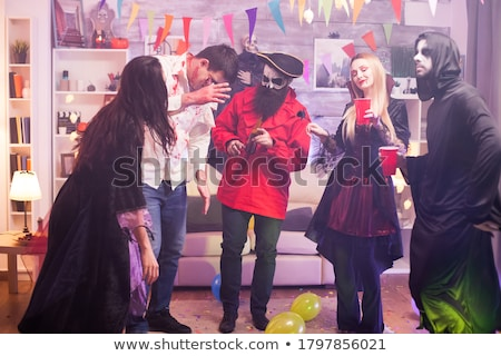 Group of joyful friends dressed in scary costumes Stock photo © deandrobot