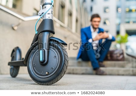 Businessman Sitting On Electric Scooter Using Cellphone Stock photo © AndreyPopov