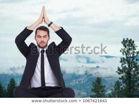 Business man meditating against foggy hills Stock photo © wavebreak_media