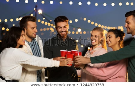 friends clinking party cups on rooftop at night Stock photo © dolgachov