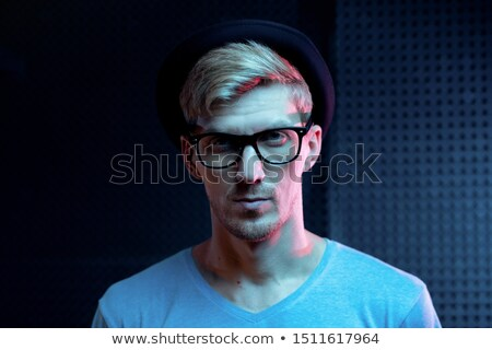 Serious young man in blue pullover, black hat and eyeglasses standing in studio Stock photo © pressmaster