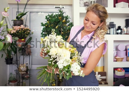 florist or seller with white lilies at flower shop Stock photo © dolgachov