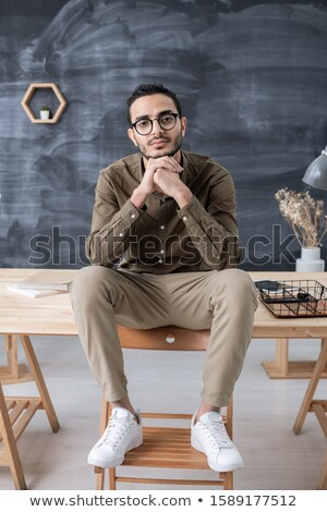 Young restful businessman in casualwear looking at you while sitting on table Stock photo © pressmaster