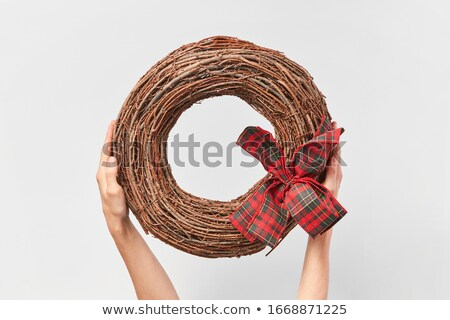 Round wreath from dry twigs with bow in a woman hand. Stock photo © artjazz