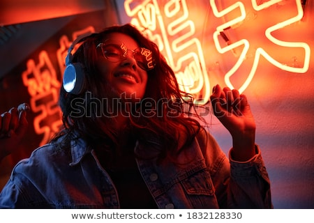 Young woman in bright light wearing sunglasses stock photo © darrinhenry