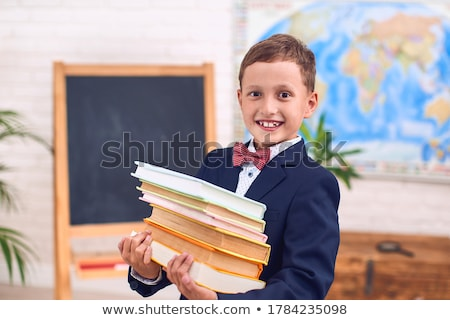 Elementary schoolboy carrying a heavy pile of books stock photo © williv