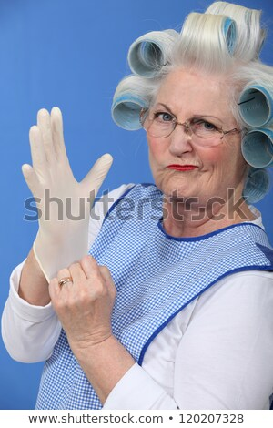Granny with her hair in rollers putting on a latex glove stock photo © photography33