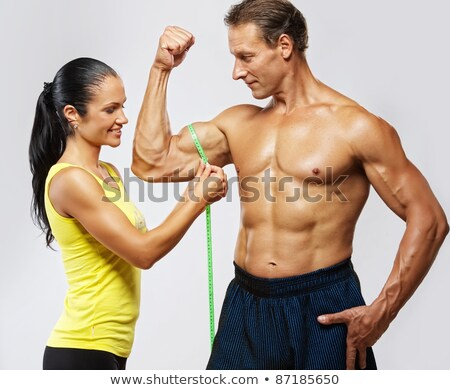 woman measuring biceps of a young man Stock photo © ambro